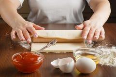 De vrouw maakt cakes in de keuken Stock Foto's