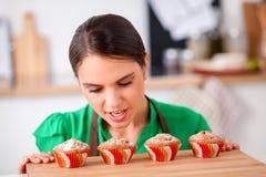 De vrouw maakt cakes in de keuken Stock Foto