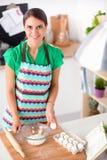 De vrouw maakt cakes in de keuken Royalty-vrije Stock Foto's