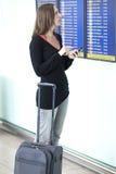De vrouw maakt controle met smartphone bij luchthaven Stock Afbeelding