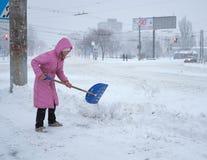 De vrouw maakt de sneeuw bij de straat van Th schoon e Stock Afbeelding