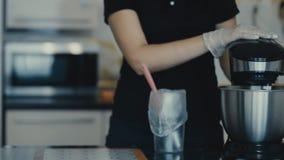 De vrouw maakt deeg binnen met mixer met duikvermogen in keuken stock videobeelden