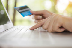 De vrouw maakt een aankoop op Internet van laptop online door credi stock afbeeldingen