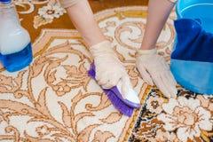 De vrouw maakt een tapijt schoon De jonge vrouw maakt een huistapijt van stof en vuil schoon Zuiverheid in het huis royalty-vrije stock afbeelding