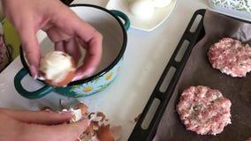 De vrouw maakt gekookte kippeneieren schoon Gehaktlapjes vlees met aardappels, eieren en kaas Kokende stappen en ingrediënten stock videobeelden