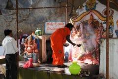 De vrouw maakt het aanbieden bij een Hindoese tempel in Hampi Stock Foto's