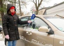 De vrouw maakt het windscherm van de sneeuwauto schoon royalty-vrije stock afbeelding