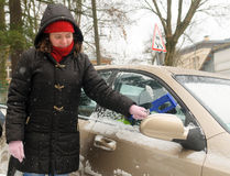 De vrouw maakt het windscherm van de sneeuwauto schoon stock foto's