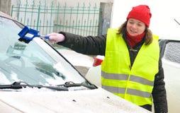 De vrouw maakt het windscherm van de sneeuwauto schoon stock fotografie