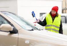 De vrouw maakt het windscherm van de sneeuwauto schoon royalty-vrije stock foto