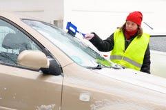 De vrouw maakt het windscherm van de sneeuwauto schoon royalty-vrije stock afbeeldingen