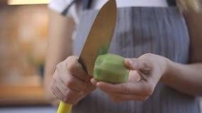 De vrouw maakt kiwi door mes, close-upvideo schoon stock video