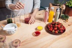 De vrouw maakt met de hand gemaakte schoonheidsmiddelen op houten lijst; stock foto's