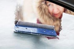 De vrouw maakt sneeuw van autoraam schoon stock fotografie