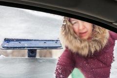 De vrouw maakt sneeuw van autoraam schoon royalty-vrije stock afbeelding