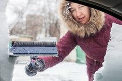 De vrouw maakt sneeuw van autoraam schoon stock foto