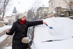 De vrouw maakt sneeuwauto schoon Stock Afbeeldingen