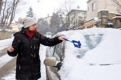 De vrouw maakt sneeuwauto schoon Royalty-vrije Stock Foto's