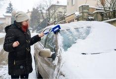 De vrouw maakt sneeuwauto schoon Royalty-vrije Stock Afbeelding