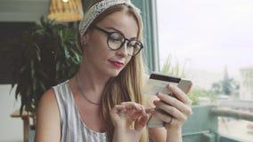 De vrouw maakt succesvolle aankoop met creditcard en mobiele telefoon Wijfje die online in koffie winkelen stock videobeelden