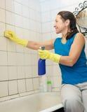 De vrouw maakt tegel met spons in badkamers schoon stock afbeelding