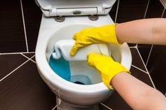De vrouw maakt toiletkom schoon gebruikend detergens stock afbeelding