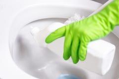De vrouw maakt toiletkom schoon gebruikend detergens stock foto's