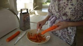 De vrouw maakt wortelen in de keuken schoon stock videobeelden