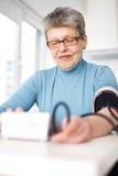 De vrouw mat haar bloeddruk royalty-vrije stock afbeelding
