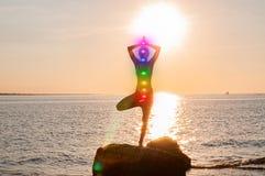 De vrouw mediteert met het gloeien zeven chakras op het strand Het silhouet van vrouw oefent yoga bij zonsondergang uit royalty-vrije stock foto