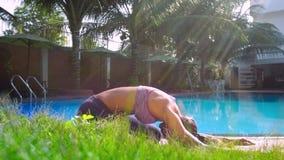 De vrouw mediteert in yoga stelt Uitgebreid Kind door pool stock video