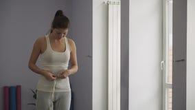 De vrouw meet de taille in de gymnastiek stock videobeelden