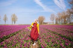 De vrouw met blond haar die een rode kleding en een gele blouse dragen die een mand met tulpen houden bloeit royalty-vrije stock afbeeldingen