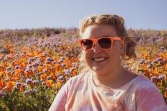 De vrouw met blonde gevlechte haar en zonnebril stelt op een papavergebied tijdens een super bloei Concept voor de lenteallergie? stock afbeeldingen