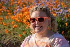 De vrouw met blonde gevlechte haar en zonnebril stelt op een papavergebied tijdens een super bloei Concept voor de lenteallergie? stock foto