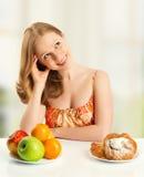 De vrouw kiest tussen gezond en ongezond voedsel Stock Foto