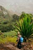 De vrouw met camera en de rugzak dichtbij één reusachtige agaveinstallatie met dor landschap van plaats riepen Corda op achtergro stock foto
