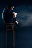 De vrouw met depressie zit op stoel Royalty-vrije Stock Foto