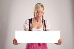 De vrouw met dirndl houdt een leeg uithangbord Stock Fotografie