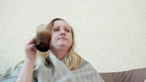 De vrouw met een koude, griep, drinkt warme thee met citroen zij hoest stock video