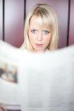 De vrouw met een krant wordt bang gemaakt Stock Foto