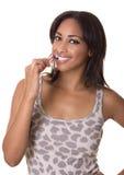 De vrouw met een richtende glimlach borstelt haar tanden. Stock Foto