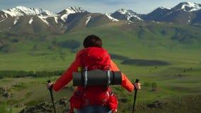 De vrouw met een rode rugzak gaat groen een zorg uit Mening van sneeuwbergen stock videobeelden