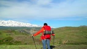 De vrouw met een rode rugzak gaat groen een zorg uit Mening van sneeuwbergen stock footage