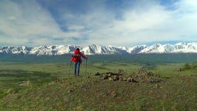 De vrouw met een rode rugzak gaat groen een zorg uit Mening van sneeuwbergen stock video