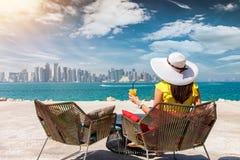 De vrouw met een sap in haar hand geniet van de mening aan de horizon van Doha, Qatar Royalty-vrije Stock Fotografie