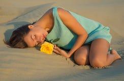 De vrouw met geel nam leugens op het zand toe stock afbeelding