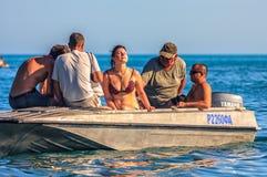 De vrouw met gesloten ogen krijgt zon, ontspant en geniet van De mensen in een kleine motorboot vertrekken voor een kustrondvaart Royalty-vrije Stock Foto's