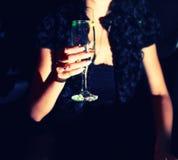 De vrouw met glas van witte wijnstok in haar dient nacht in Stock Afbeeldingen