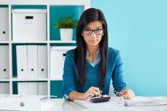 De vrouw met glazen berekent belasting bij bureau Stock Foto's